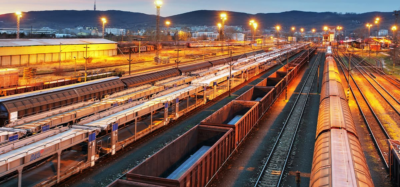 Rail yard at dusk with a mountain range in the background